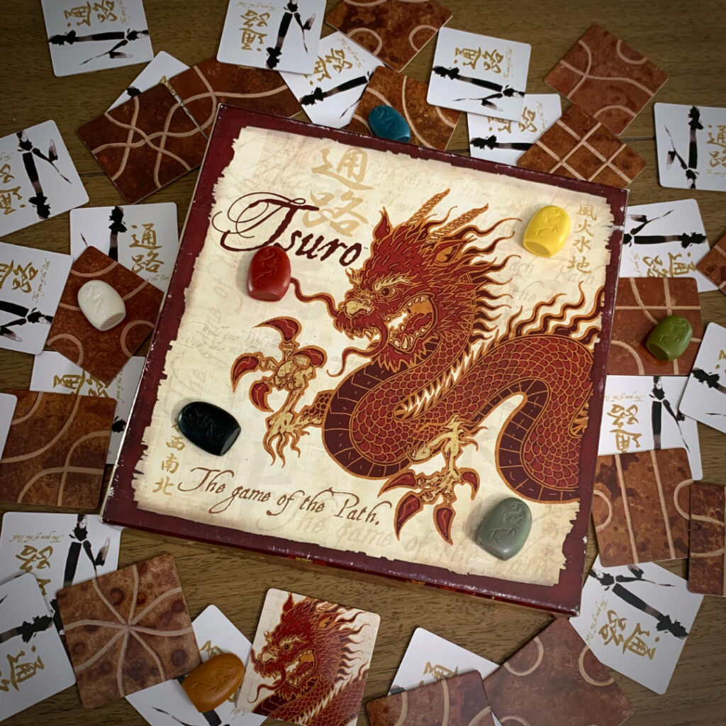 Artistic image of the Tsuro box surrounded by game tiles